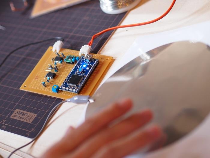 広告ポスターへの応用を視野に、現在試作中のタッチパッド。A4の紙に描かれた銀色の丸い部分が電極(タッチセンサー)で、それに触れると青のLEDが点灯する。直接触れるだけでなく、紙の上から触れてもLEDを点灯させることができる。