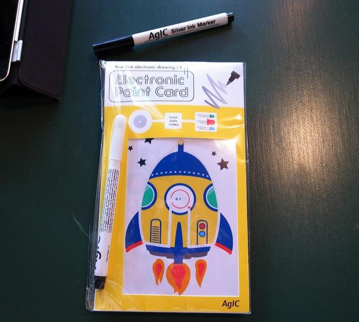 この春、アメリカのイベントで販売し好評だった「子ども向け電子工作キット」(発売未定)。導電性ペン、電池、LEDなどが入っていて、紙の上の点線を導電性ペンでなぞると、ロケットが光るカードが完成する。