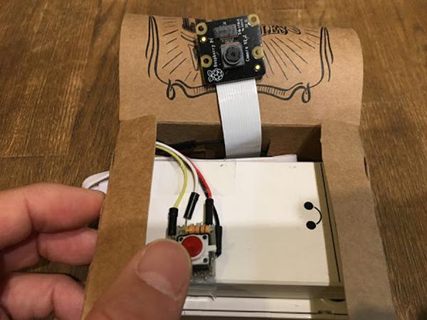 紙製の箱の中に、ラズパイ、バッテリー、カメラ、ボタンなどを収納