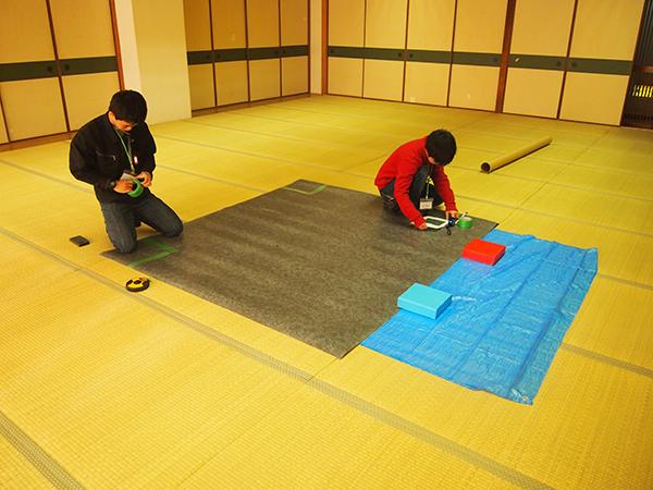 黙々と会場準備を行う、ミニロボコン担当幹事の佐々木さん(写真左)。